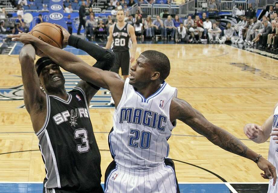 Orlando Magic's DeQuan Jones (20) fouls San Antonio Spurs' Stephen Jackson (3) while going after a rebound during the first half of an NBA preseason basketball game, Sunday, Oct. 21, 2012, in Orlando, Fla. (AP Photo/John Raoux)