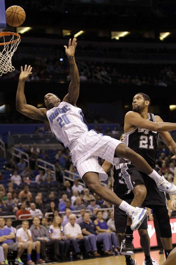 Orlando Magic's DeQuan Jones (20) falls backward while shooting after he was fouled by San Antonio Spurs' Tim Duncan (21) during the first half of an NBA preseason game Sunday, Oct. 21, 2012, in Orlando, Fla. (AP Photo/John Raoux)