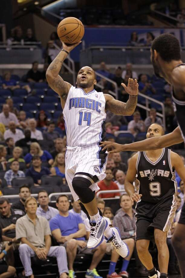 Orlando Magic's Jameer Nelson (14) goes up for a shot past San Antonio Spurs' Tony Parker (9), of France, and power forward Tim Duncan, right, during the first half of an NBA preseason basketball game, Sunday, Oct. 21, 2012, in Orlando, Fla. (AP Photo/John Raoux)