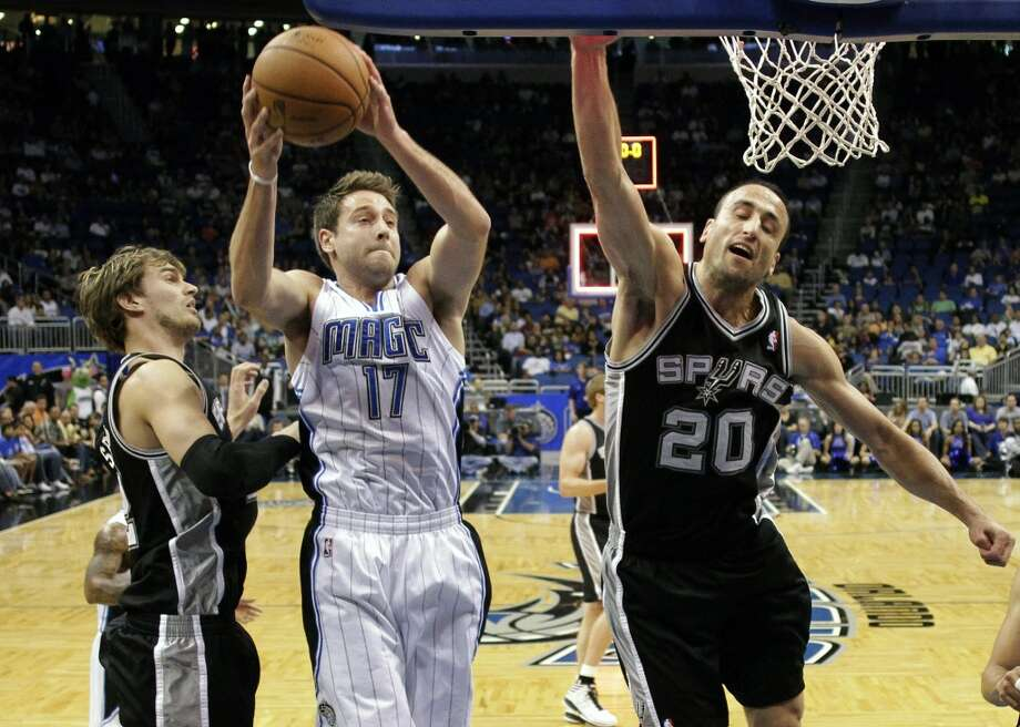 Orlando Magic's Josh McRoberts (17) grabs a rebound away from San Antonio Spurs' Tiago Splitter, left, of Brazil, and San Antonio Spurs' Manu Ginobili (20), of Argentina, during the first half of an NBA preseason basketball game, Sunday, Oct. 21, 2012, in Orlando, Fla. (AP Photo/John Raoux)