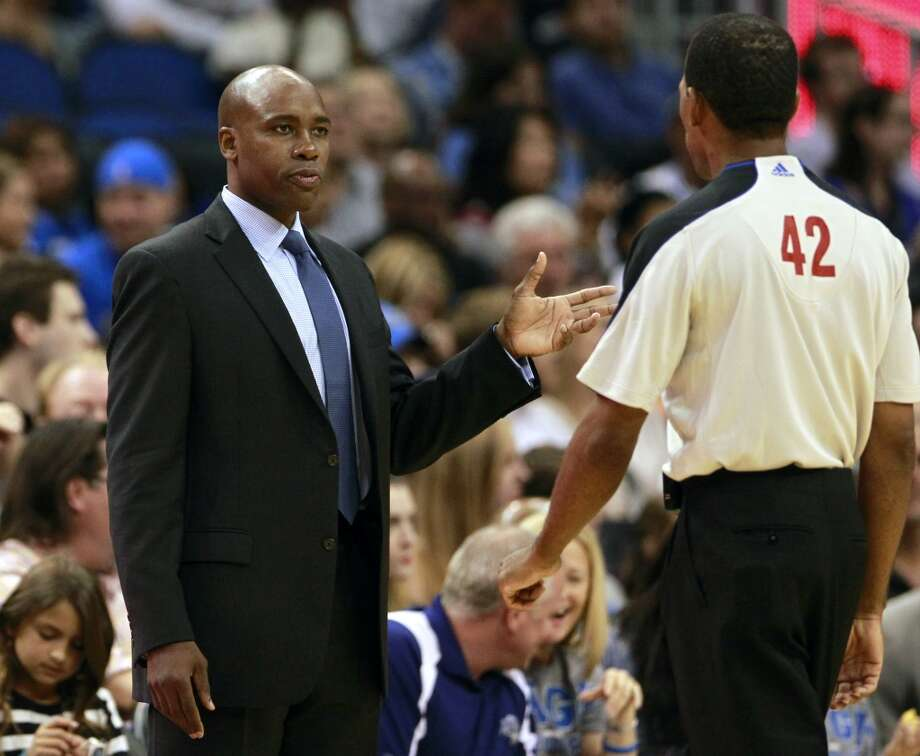 Orlando Magic head coach Jacque Vaughn, left, has words with official Eric Lewis (42) during the first half of an NBA preseason basketball game against the San Antonio Spurs, Sunday, Oct. 21, 2012, in Orlando, Fla. (AP Photo/John Raoux)