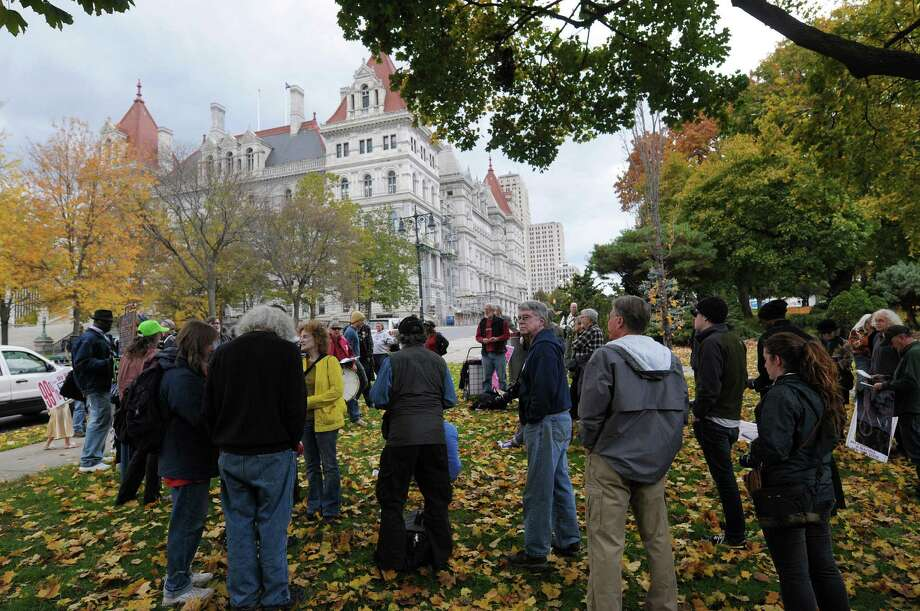 With the capitol seen in the background people gather in Academy Park as members of Occupy Albany marched to the park to mark their one year anniversary of the start of the Occupy Albany movement on Sunday, Oct. 21, 2012 in Albany, NY.    (Paul Buckowski / Times Union) Photo: Paul Buckowski