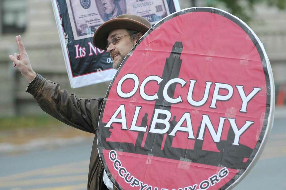 Bradley Russell of Albany gives the peace sign to drivers passing by  Academy Park as members of Occupy Albany marched to the park to mark their one year anniversary of the start of the Occupy Albany movement on Sunday, Oct. 21, 2012 in Albany, NY.    (Paul Buckowski / Times Union) Photo: Paul Buckowski