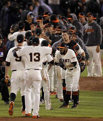 Sergio Romo, lower right, high fives teammates after the Giants' victory over the Cardinals in Game 6. The San Francisco Giants played the St. Louis Cardinals in Game 6 of the National League Championship Series at AT&T Park on Sunday, October 21, 2012, in San Francisco, Calif., The Giants defeated the Cardinals 6-1 to stay alive in the series and force a game 7. Photo: Carlos Avila Gonzalez, The Chronicle