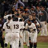 Sergio Romo, lower right, high fives teammates after the Giants' victory over the Cardinals in Game 6. The San Francisco Giants played the St. Louis Cardinals in Game 6 of the National League Championship Series at AT&T Park on Sunday, October 21, 2012, in San Francisco, Calif., The Giants defeated the Cardinals 6-1 to stay alive in the series and force a game 7.