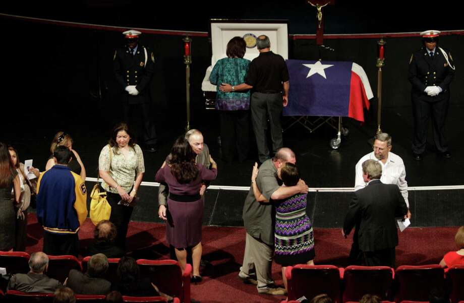 Theresa Moreno Gallegos, center left in purple dress, hugs a mourner during the visitation and rosary for her husband. Photo: Melissa Phillip / © 2012 Houston Chronicle