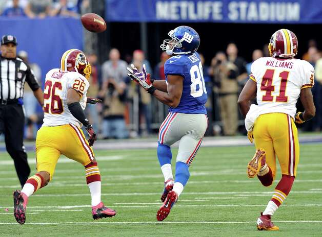 New York Giants wide receiver Victor Cruz (80) catches a pass as Washington Redskins cornerback Josh Wilson (26) and Madieu Williams pursue him during the second half of an NFL football game on Sunday, Oct. 21, 2012, in East Rutherford, N.J. The Giants won the game 27-23. (AP Photo/Bill Kostroun) Photo: Bill Kostroun