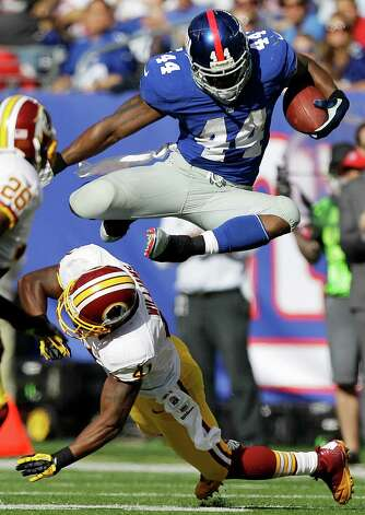 New York Giants running back Ahmad Bradshaw, top, leaps over Washington Redskins free safety Madieu Williams (41) for a first down during the second half of an NFL football game on Sunday, Oct. 21, 2012, in East Rutherford, N.J. The Giants won the game 27-23. (AP Photo/Kathy Willens) Photo: Kathy Willens