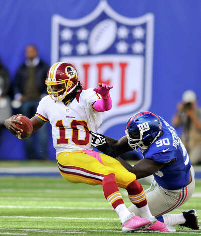 Washington Redskins quarterback Robert Griffin III (10) is sacked by New York Giants defensive end Jason Pierre-Paul (90) during the second half of an NFL football game, Sunday, Oct. 21, 2012, in East Rutherford, N.J. (AP Photo/Bill Kostroun) Photo: Bill Kostroun