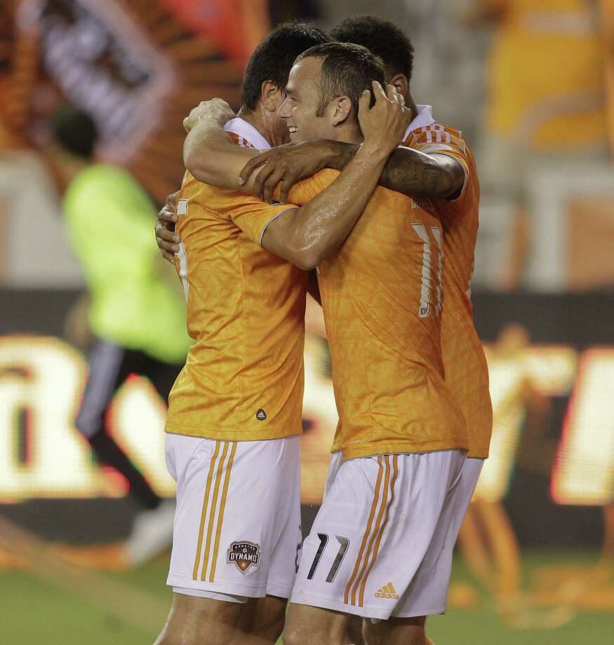 HOUSTON,TX - OCTOBER 20: Brad Davis #11 is congratulated by Brian Ching #25 and Giles Barnes #23 of the Houston Dynamo after scoring on a penalty kick in the second half against the Philadelphia Union at BBVA Compass Stadium on October 20, 2012 in Houston, Texas. Houston won 3-1. Photo: Bob Levey, Getty Images / 2012 Getty Images