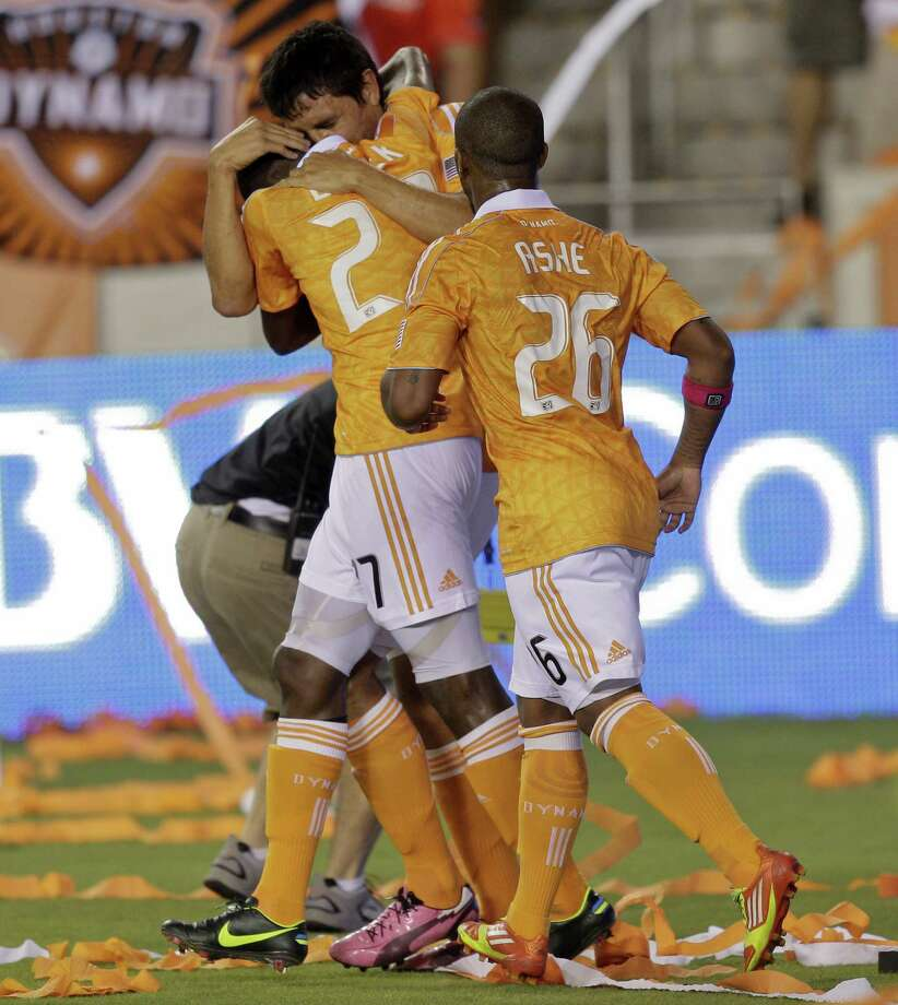 HOUSTON,TX - OCTOBER 20:  Brian Ching #25 gives Boniek Garcia #27 of the Houston Dynamo a hug after scoring in the second half against the Philadelphia Union as Corey Ashe #26 of the Houston Dynamo looks on at BBVA Compass Stadium on October 20, 2012 in Houston, Texas. Houston won 3-1. Photo: Bob Levey, Getty Images / 2012 Getty Images