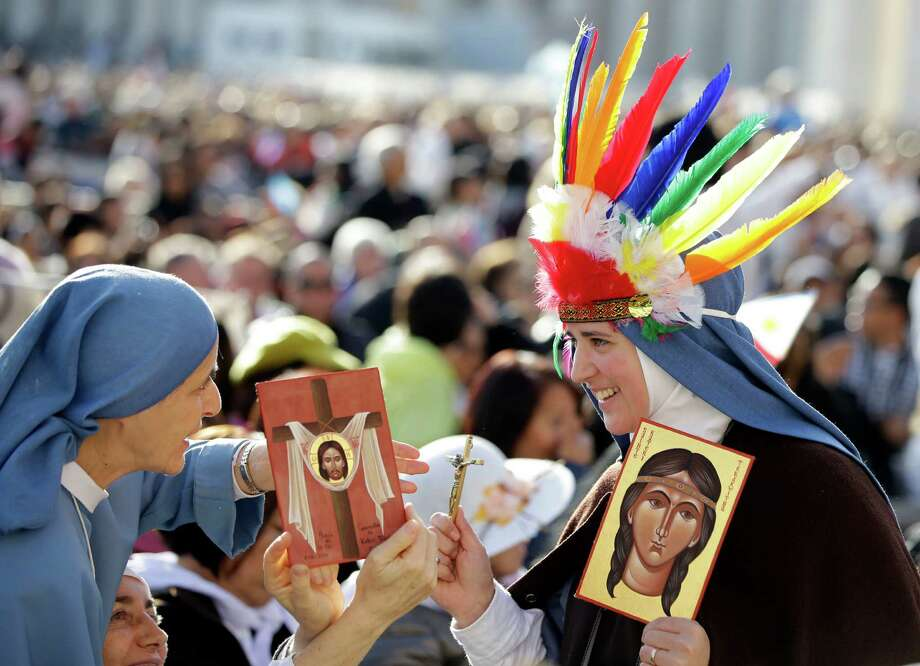 Two nuns hold images of Kateri Tekakwitha, the first Native American to achieve sainthood, as they wait for the start of a canonization ceremony celebrated by Pope Benedict XVI, in St. Peter's Square, at the Vatican, Sunday, Oct. 21, 2012. The pontiff will canonize seven people, Kateri Tekakwitha, Maria del Carmen, Pedro Calungsod, Jacques Berthieu, Giovanni Battista Piamarta, Mother Marianne Cope, and Anna Shaeffer. (AP Photo/Andrew Medichini) Photo: Andrew Medichini