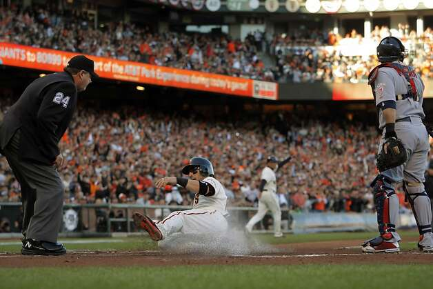 Marco Scutaro scores on a fielder's choice on a ball hit by Buster Posey in the first inning. The San Francisco Giants played the St. Louis Cardinals in Game 6 of the National League Championship Series at AT&T Park on Sunday, October 21, 2012, in San Francisco, Calif., The Giants defeated the Cardinals 6-1 to stay alive in the series and force a game 7. Photo: Carlos Avila Gonzalez, The Chronicle