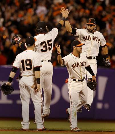 Angel Pagan went high in the air to congratulate 35 Brandon Crawford as Gregor Blanco (center) and 19 Marco Scutaro joined the celebration at the end of the game. The San Francisco Giants defeated the St. Louis Cardinals 6-1 to tie up the NLCS series at AT&T park in San Francisco, Calif. Sunday October 21, 2012. Photo: Brant Ward, The Chronicle