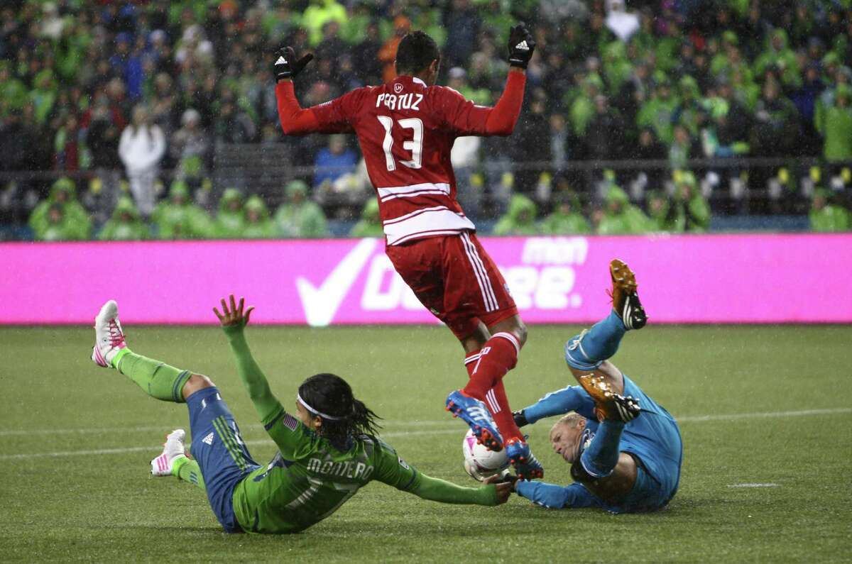 Sounders player Fredy Montero tangles with FC Dallas goalie Kevin Hartman and Hernan Pertuz (13) in a play that resulted in a Sounders penalty kick and goal in the first half. The Sounders won 3-1 in their final regular-season home game.