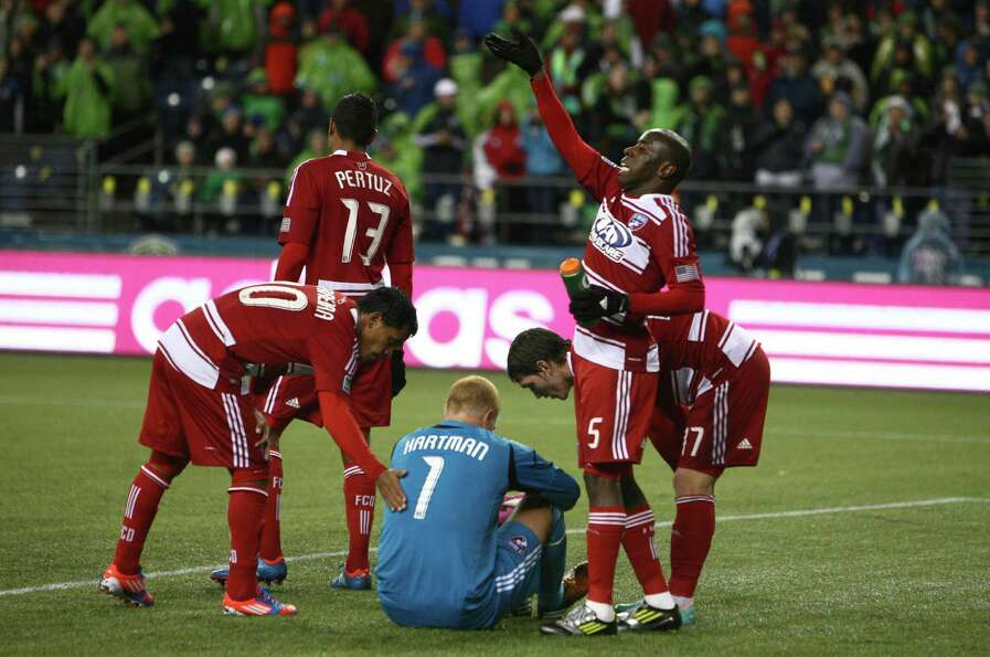 FC Dallas players tend to goalkeeper Kevin Hartman after he took a ball to the face.