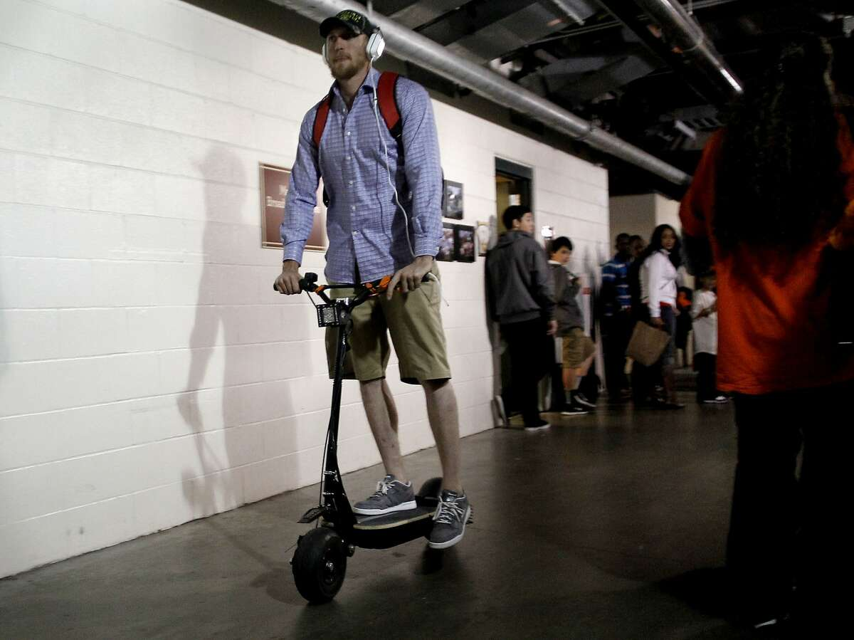 Giants' Hunter Pence rides his electric scooter away from the clubhouse after the San Francisco Giants beat the St. Louis Cardinals 6-1 in game six of the National League Championship Series, on Sunday Oct. 21, 2012 at AT&T Park, in San Francisco, Calif.
