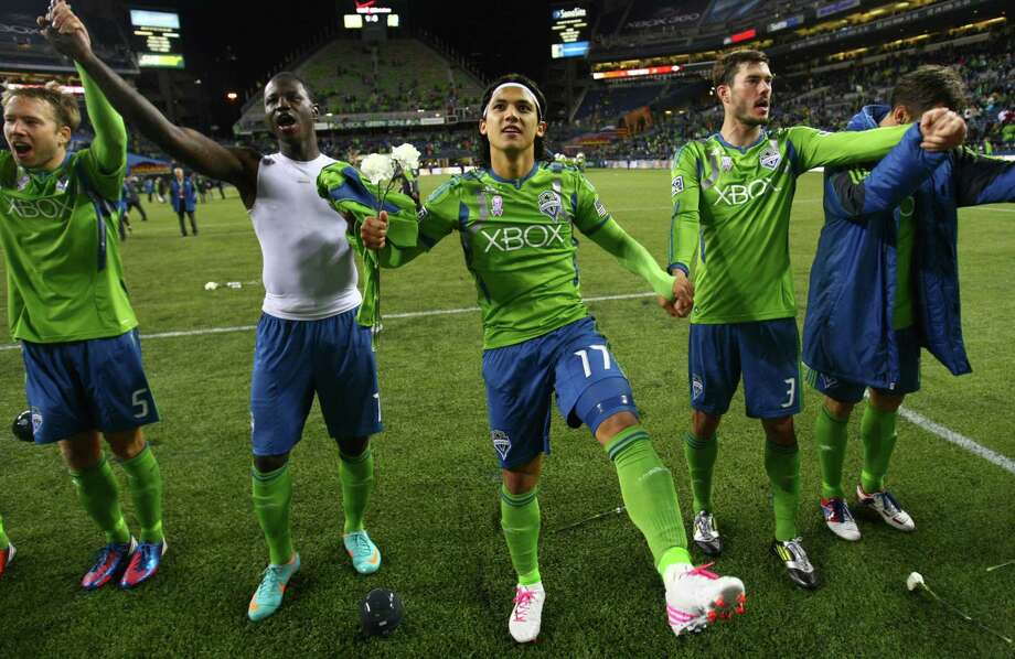Sounders players, from left, Adam Johansson, Eddie Johnson, Fredy Montero and Brad Evans thank fans after the game. Photo: JOSHUA TRUJILLO / SEATTLEPI.COM