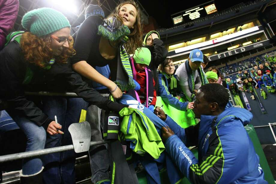 Sounders player Eddie Johnson signs autographs for fans after the game. Photo: JOSHUA TRUJILLO / SEATTLEPI.COM