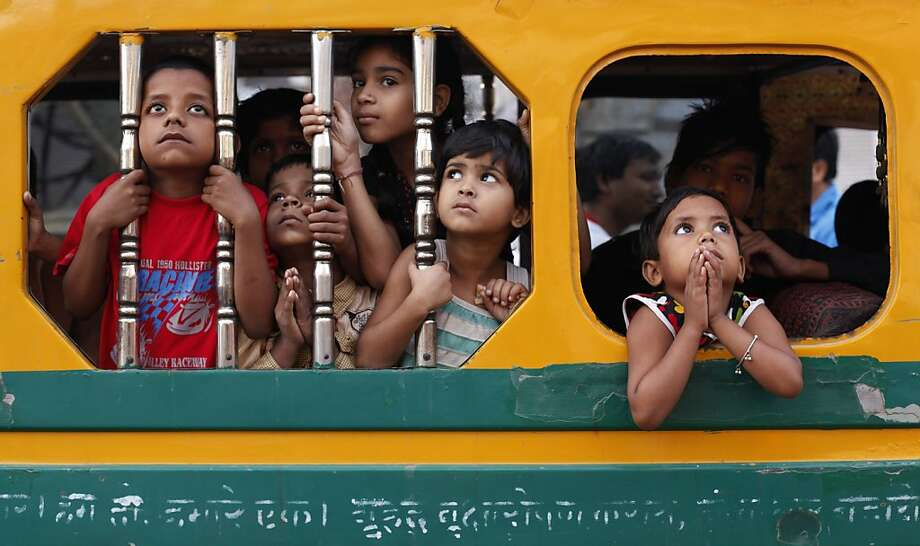Indian children watch a Dussehra festival procession early morning in Allahabad, India, Sunday, Oct. 21, 2012. The Hindu festival Dussehra commemorates the triumph of Lord Rama over the demon king Ravana, marking the victory of good over evil. (AP Photo/Rajesh Kumar Singh) Photo: Rajesh Kumar Singh, Associated Press