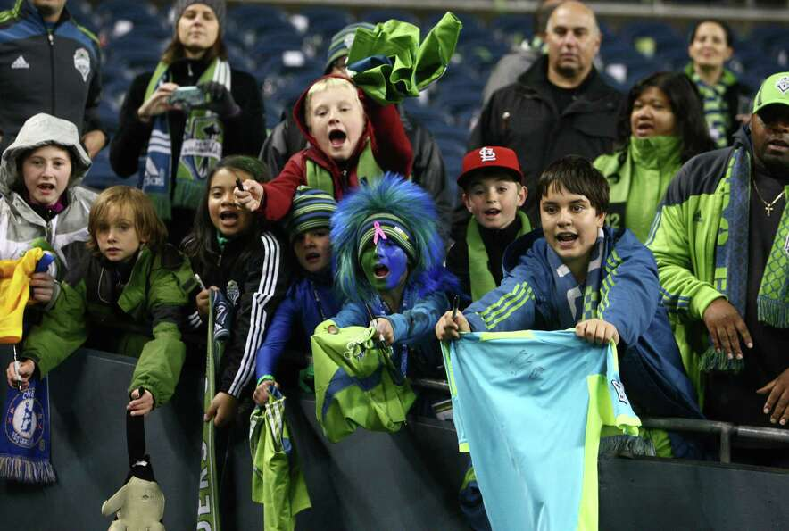 Sounders fans try to get autographs after the game.