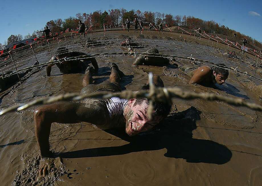ENGLISHTOWN, NJ - OCTOBER 21:  Participants go through the Kiss of Mud obstacle at the Tough Mudder event at Raceway Park on October 21, 2012 in Englishtown, New Jersey.  (Photo by Bruce Bennett/Getty Images) ***BESTPIX*** Photo: Bruce Bennett, Getty Images