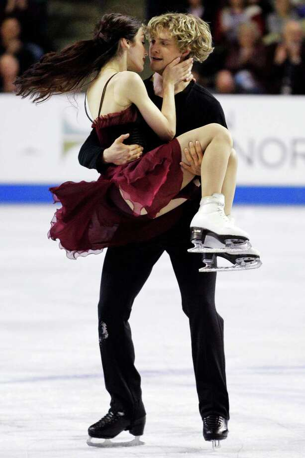 Charlie White picks up Meryl Davis and after their first-place finish in the ice dance event. Photo: AP