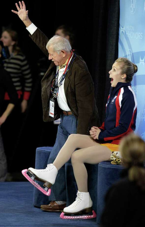 Ashley Wagner, right, reacts to her scores along with her coach, John Nicks, left, after winning the gold medal in the ladies free event. Photo: AP