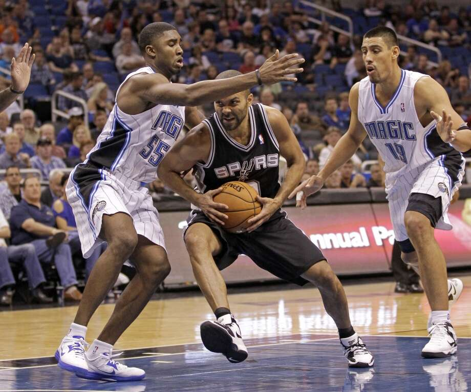 San Antonio Spurs' Tony Parker, of France, center, makes a move to the basket between Orlando Magic's E'Twaun Moore (55) and Gustavo Ayon (19), of Mexico, during the second half of an NBA preseason basketball game, Sunday, Oct. 21, 2012, in Orlando, Fla. Orlando won 104-100.(AP Photo/John Raoux)