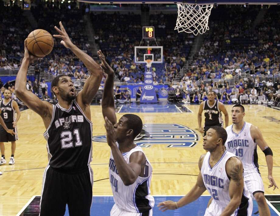 San Antonio Spurs' Tim Duncan (21) takes a shot over Orlando Magic's Andrew Nicholson (44) as Justin Harper (32) and Gustavo Ayon (19), of Mexico, look on, during the first half of an NBA preseason basketball game, Sunday, Oct. 21, 2012, in Orlando, Fla. Orlando won 104-100.(AP Photo/John Raoux)
