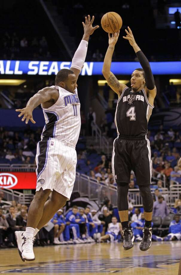 San Antonio Spurs shooting guard Danny Green (4) takes a shot over Orlando Magic's Glen Davis (11) during the second half of an NBA preseason basketball game, Sunday, Oct. 21, 2012, in Orlando, Fla. Orlando won 104-100.(AP Photo/John Raoux)
