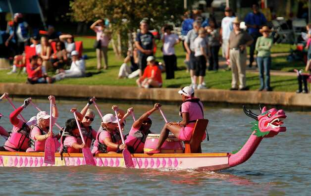 Pink Phurree, a breast cancer survivor dragon boat team, paddles down the lake during the first round of races of the 8th annual Gulf Coast International Dragon Boat Regatta at Brooks Lake on a sunny Saturday, Oct. 20, 2012, in Sugar Land.  Photo: Mayra Beltran, . / © 2012 Houston Chronicle