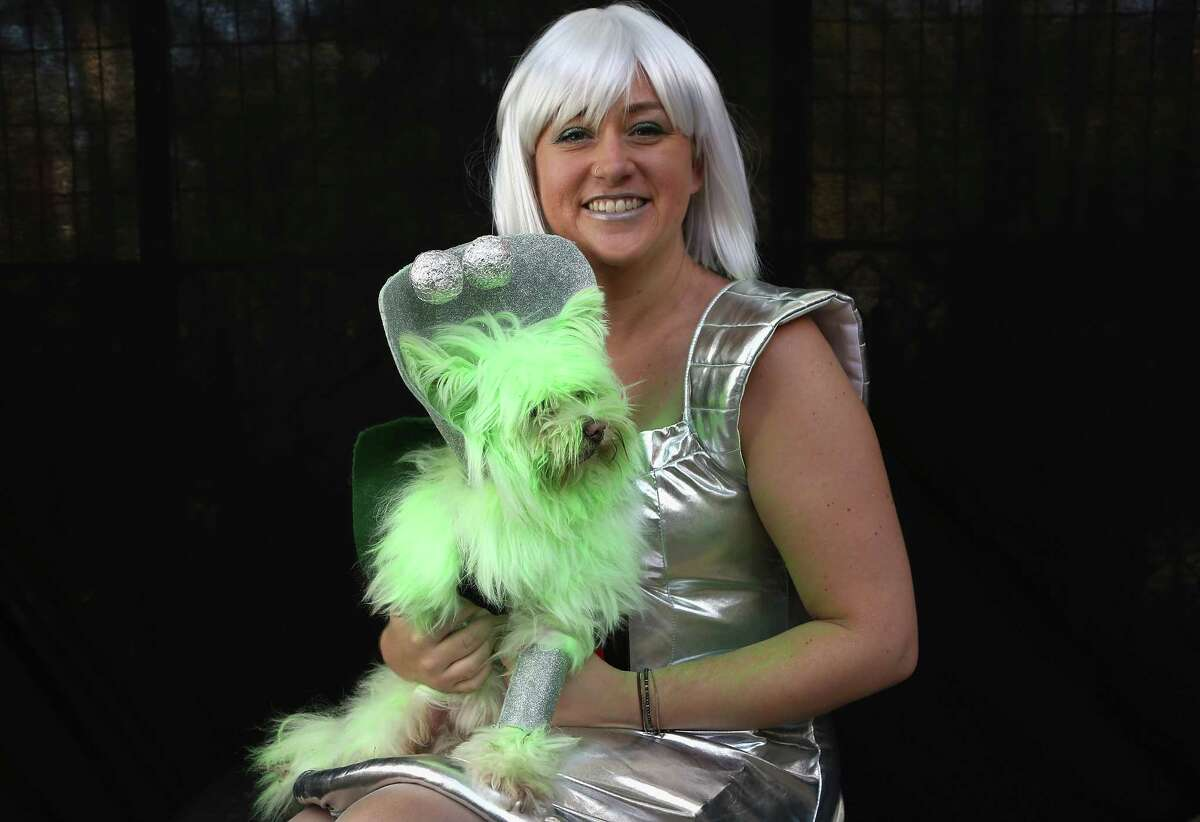 NEW YORK, NY - OCTOBER 20: Nichole Hallberg holds her dog Wilson, a rescued mixed breed posing as a Martian, at the Tompkins Square Halloween Dog Parade on October 20, 2012 in New York City. Hundreds of dog owners festooned their pets for the annual event, the largest of its kind in the United States.