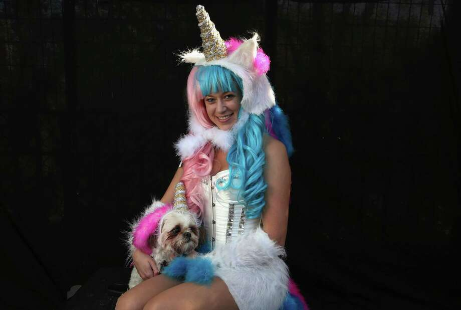 NEW YORK, NY - OCTOBER 20:  Jamae Hallberg and her Shih Tsu Femma pose as unicorns at the Tompkins Square Halloween Dog Parade on October 20, 2012 in New York City. Hundreds of dog owners festooned their pets for the annual event, the largest of its kind in the United States. Photo: John Moore, Getty Images / 2012 Getty Images