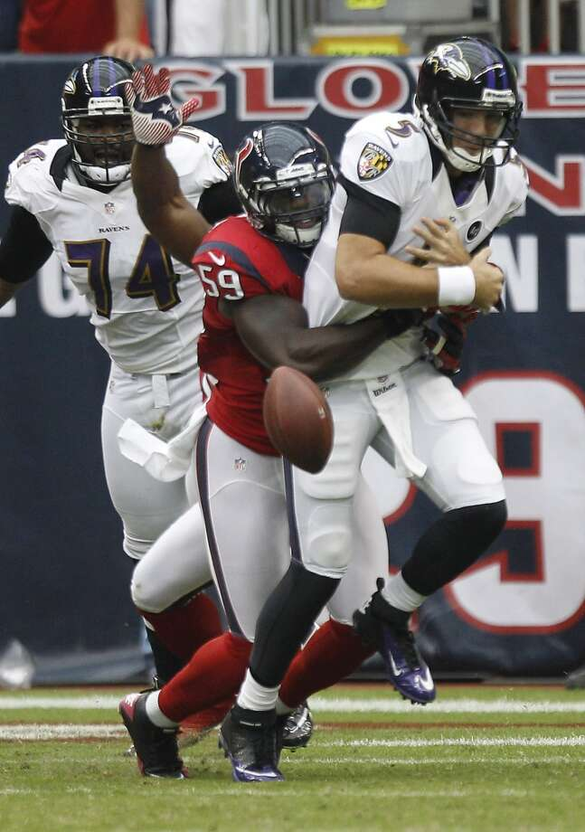 Ravens quarterback Joe Flacco (5) has the ball stripped from him by Houston Texans linebacker Whitney Mercilus (59) during the first quarter. (Brett Coomer / Houston Chronicle)