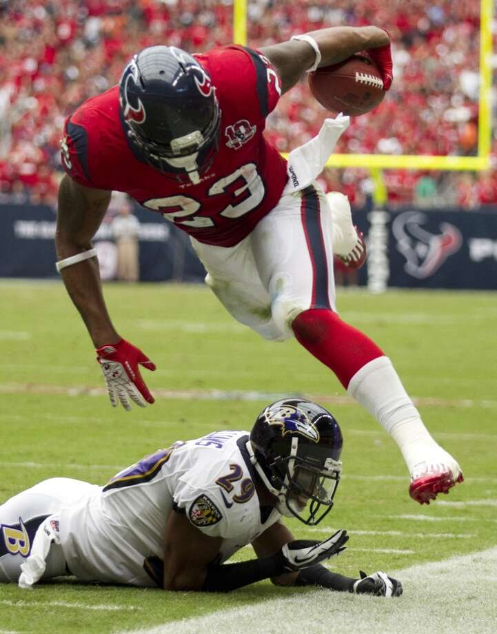 Texans running back Arian Foster (23) is tripped up by Baltimore Ravens cornerback Cary Williams (29) during the third quarter. (Brett Coomer / Houston Chronicle)