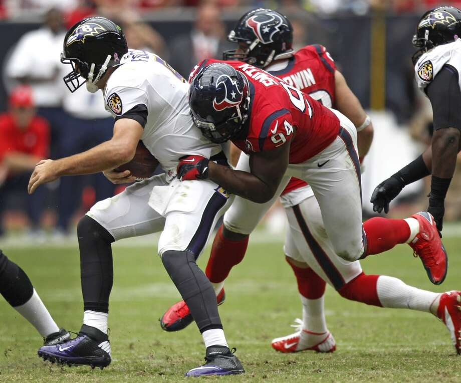 Ravens quarterback Joe Flacco (5) is sacked by Texans defensive end Antonio Smith (94) during the fourth quarter. (Brett Coomer / Houston Chronicle)