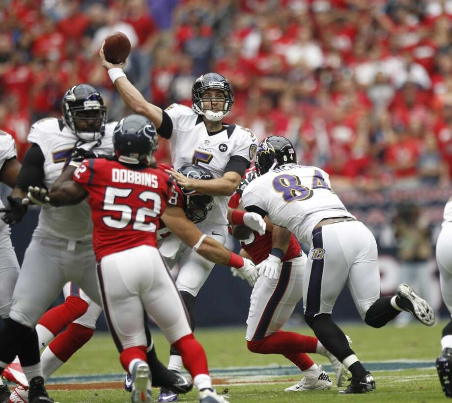 Ravens quarterback Joe Flacco (5) gets off a pass as he is hit by Houston Texans defensive end J.J. Watt (99) during the first quarter. (Brett Coomer / Houston Chronicle)