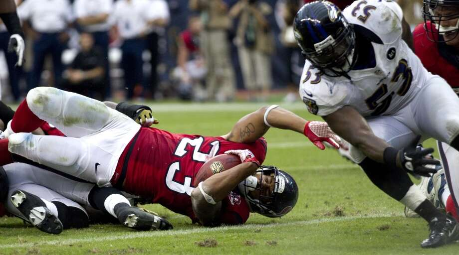 Texans running back Arian Foster (23) reaches across the goal line for a 2-yard touchdown run as Ravens inside linebacker Jameel McClain (53) comes in to defend during the fourth quarter. (Brett Coomer / Houston Chronicle)
