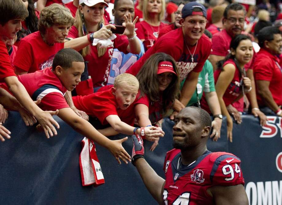 Texans defensive end Antonio Smith (94) high-fives with the fans after the Texans beat the Ravens at Reliant Stadium. (Brett Coomer / Houston Chronicle)