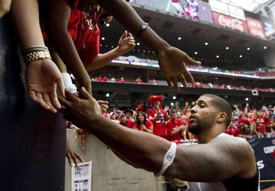 Texans running back Arian Foster high-fives fans as he leaves the field after the Texans beat the Ravens. (Brett Coomer / Houston Chronicle)