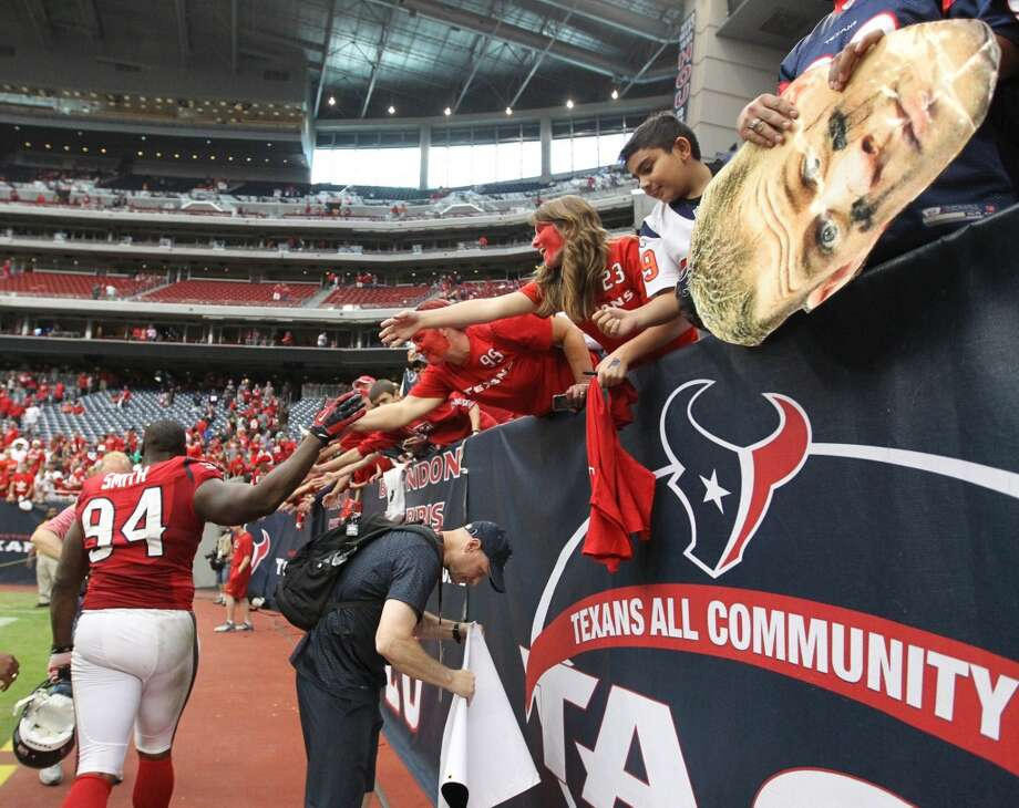 Texans defensive end Antonio Smith (94) celebrates with fans as he heads to the locker room after the win. (Karen Warren / Houston Chronicle)