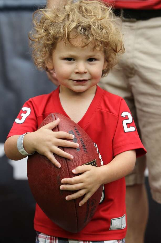 Logan Goldstein, 2 1/2, stands on the sidelines before the start of the game. (Karen Warren / Houston Chronicle)