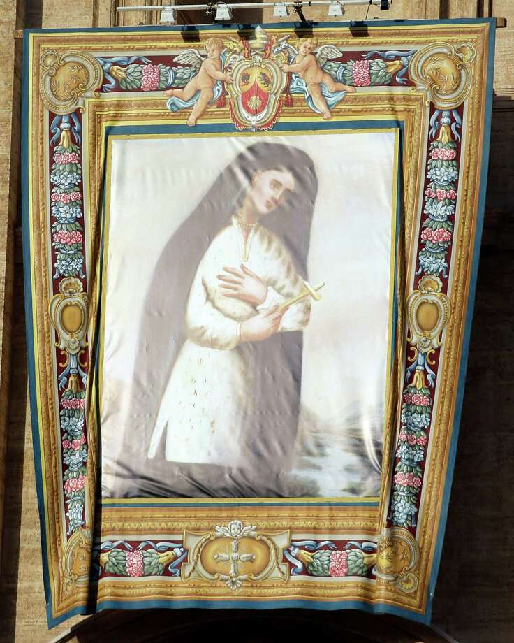 The tapestry of Kateri Tekakwitha, the first American Indian to achieve sainthood, hangs from St. Peter's Basilica at the Vatican as Pope Benedict XVI celebrates a canonization ceremony, Sunday, Oct. 21, 2012. Tekakwitha, a 17th-century Mohawk Indian who spent most of her life in what is now upstate New York, was declared a saint by the pontiff along with six others during the ceremony. Photo: Andrew Medichini, AP / AP