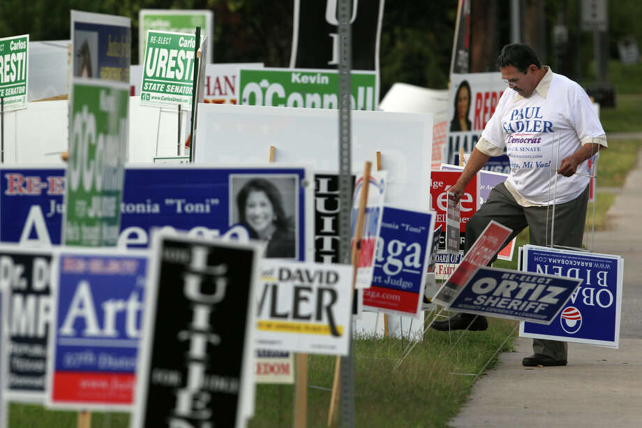 David Zepeda, (right) a volunteer for the Democratic Party, sets up signs on the first day of early voting Monday October 22, 2012 at the Brookhollow Public Library on Heimer road. Early voting ends November 2 and election day is November 6. Photo: JOHN DAVENPORT, San Antonio Express-News / ©San Antonio Express-News/Photo Can Be Sold to the Public