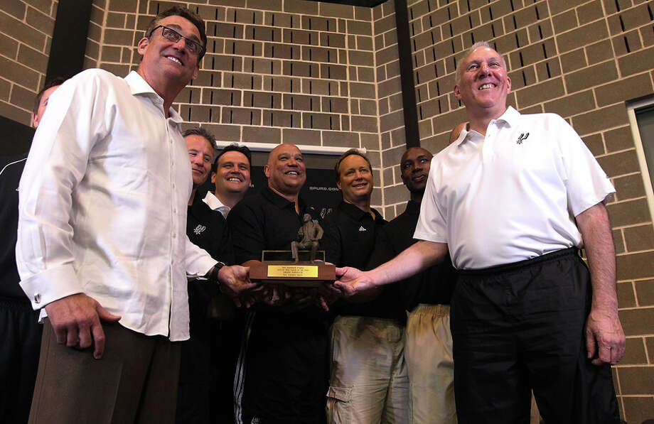 Spurs head coach Gregg Popovich (right) receives the Red Auerbach trophy for being chosen as the 2011-12 NBA coach of the year on Tuesday, May 1, 2012. Popovich was joined by his staff along with Spurs General Manager R.C. Buford (front left) for the announcement at their training facility. Kin Man Hui/Express-News. Photo: KIN MAN HUI, SAN ANTONIO EXPRESS-NEWS / ©2012 San Antonio Express-News