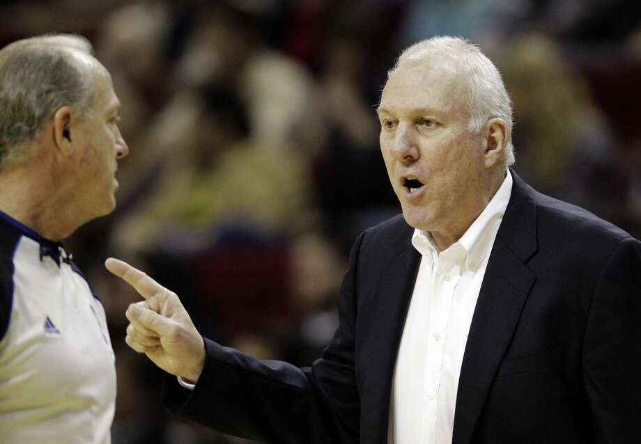 San Antonio Spurs coach Gregg Popovich, right, talks to official Kevin Fehr, left, during the second quarter of an NBA basketball game against the Houston Rockets, Thursday, Dec. 29, 2011, in Houston. (AP Photo/David J. Phillip) Photo: David J. Phillip, AP / AP