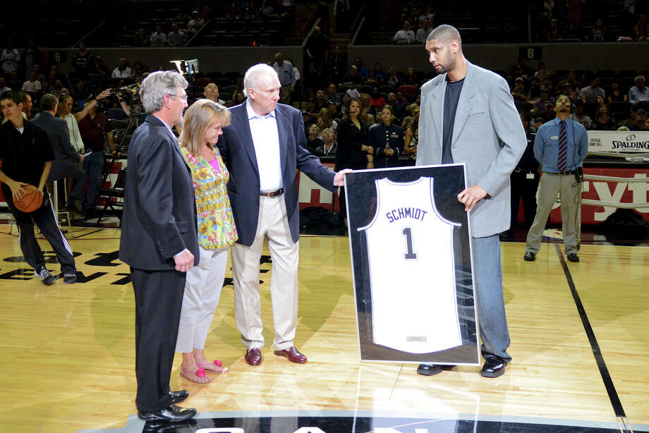 San Antonio Spurs center Tim Duncan (right) and San Antonio Spurs head coach Gregg Popovich present a jersey to David R. Schmidt, M.D. and Becky Whetstone, Ph.D who's son Marine Lance Cpl. Benjamin Whetstone Schmidt was killed during a combat mission in the Helmand province in Afghanistan, where he was a scout sniper, on October 6, 2011. The presentation was made before a NBA basketball game between the Philadelphia 76ers and the San Antonio Spurs at the AT&T Center in San Antonio, Texas on March 25, 2012.John Albright / Special to the Express-News. Photo: JOHN ALBRIGHT, San Antonio Express-News / San Antonio Express-News