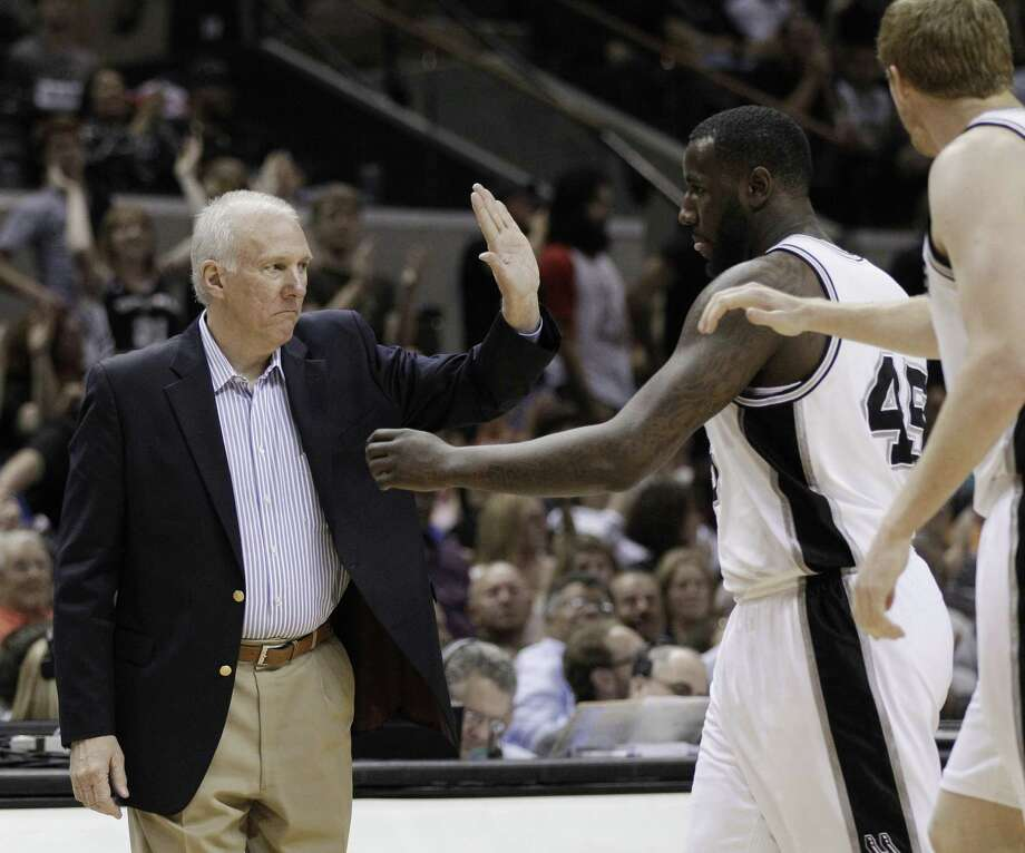 San Antonio Spurs coach Gregg Popovich, left, greets his players during a timeout in the fourth quarter of an NBA basketball game against the Portland Trail Blazers, Monday, April 23, 2012, in San Antonio. San Antonio won 124-89, clinching the top seed in the Western Conference. (AP Photo/Eric Gay) Photo: Eric Gay, AP / AP