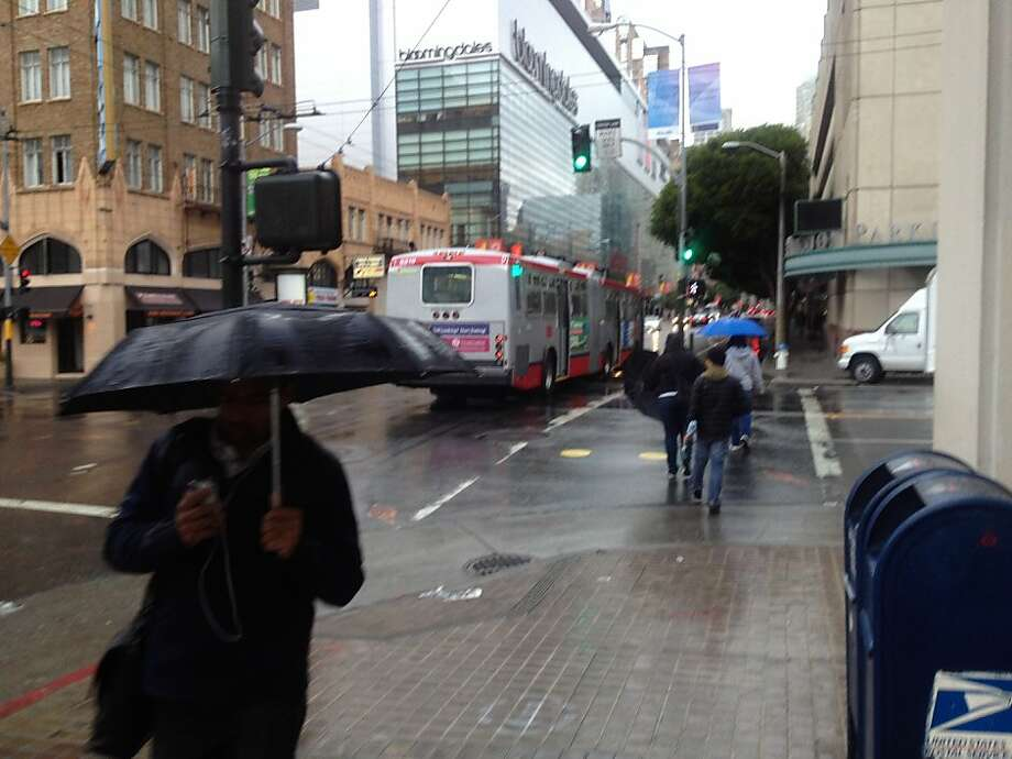 Pedestrians walk through the season's first rainfall at the corner of 5th and Mission Streets on Monday morning, Oct. 22, 2012. Photo: Will Kane, The Chronicle